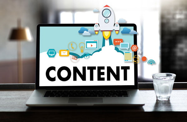 Laptop screen with vector images and 'Content' written on it - SEO content writing in 2020