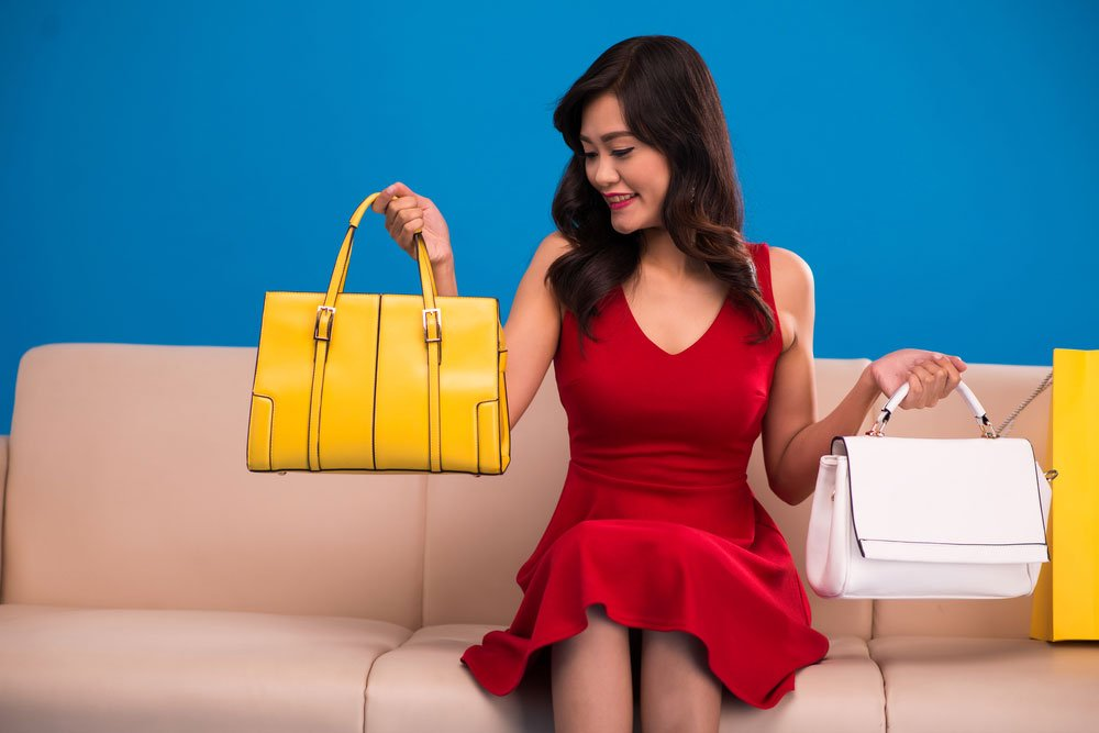 Woman holding two handbags, comparing them