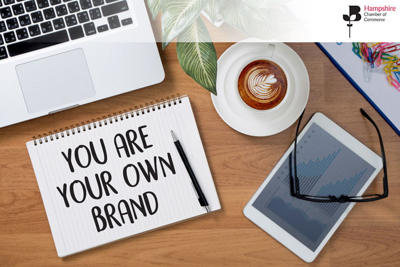 A spiral notebook with the words 'You are your own brand' written on it, lying next to a laptop kyeboard, tablet, and a cup of coffee, with some colourful paper clips in the top right corner