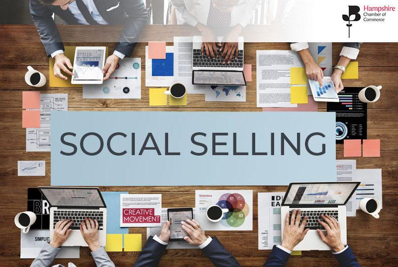 Social selling written on a backdrop of a wooden table with people around it